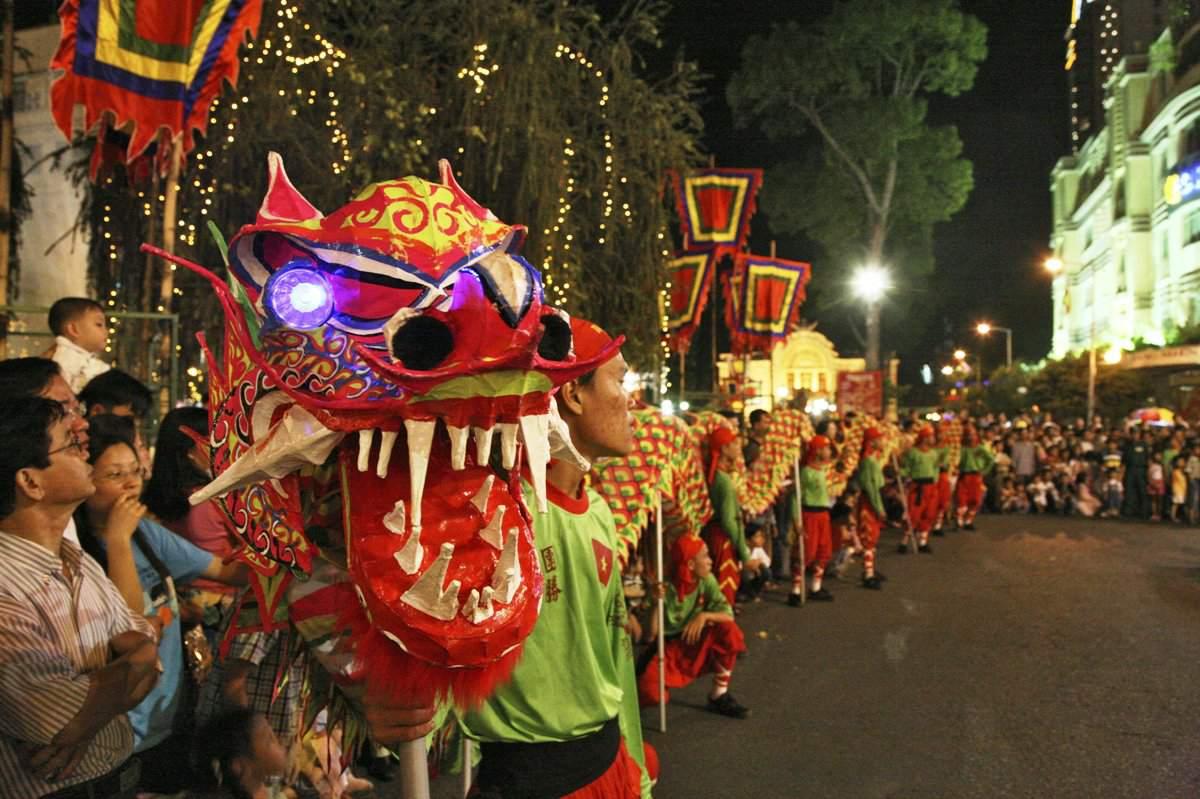 People at dragon dance during Tet festival at night, Saigon, Vietnam