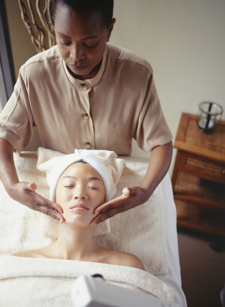 Woman massaging woman's face at spa