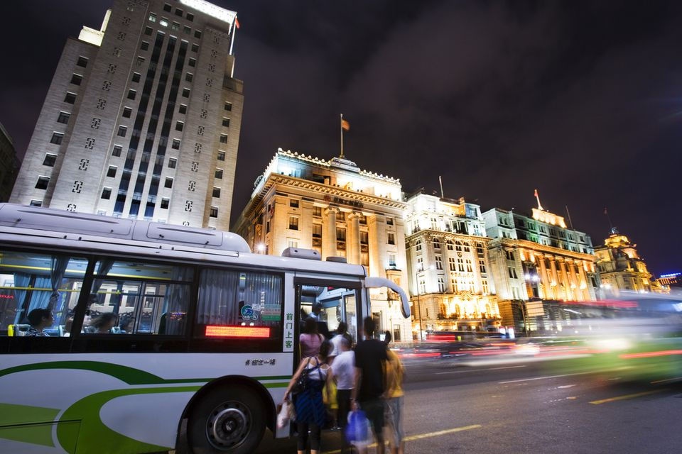 Bus picking up passengers on the Bund at night