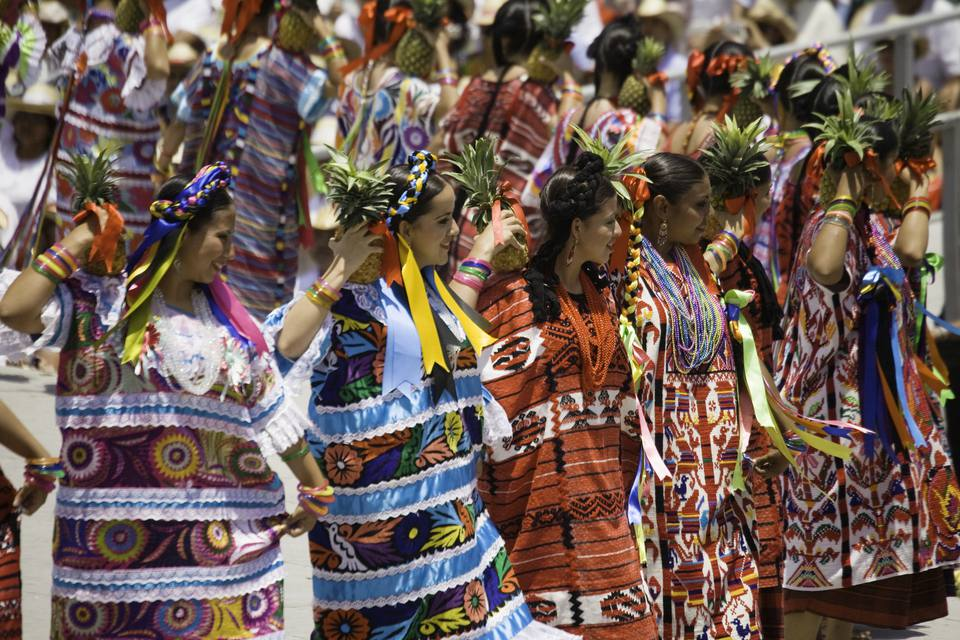 Las mujeres que sostienen la piña y bailan en fila durante la Flor de Piña, sonríen
