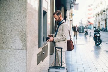 Man getting money from atm with luggage and wallet