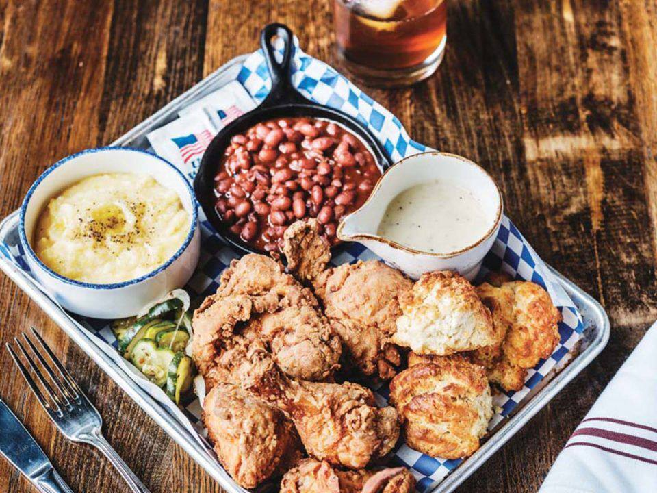 A full platter of food including fried chicken, biscuits and gravy, grits, and baked beans at Julep