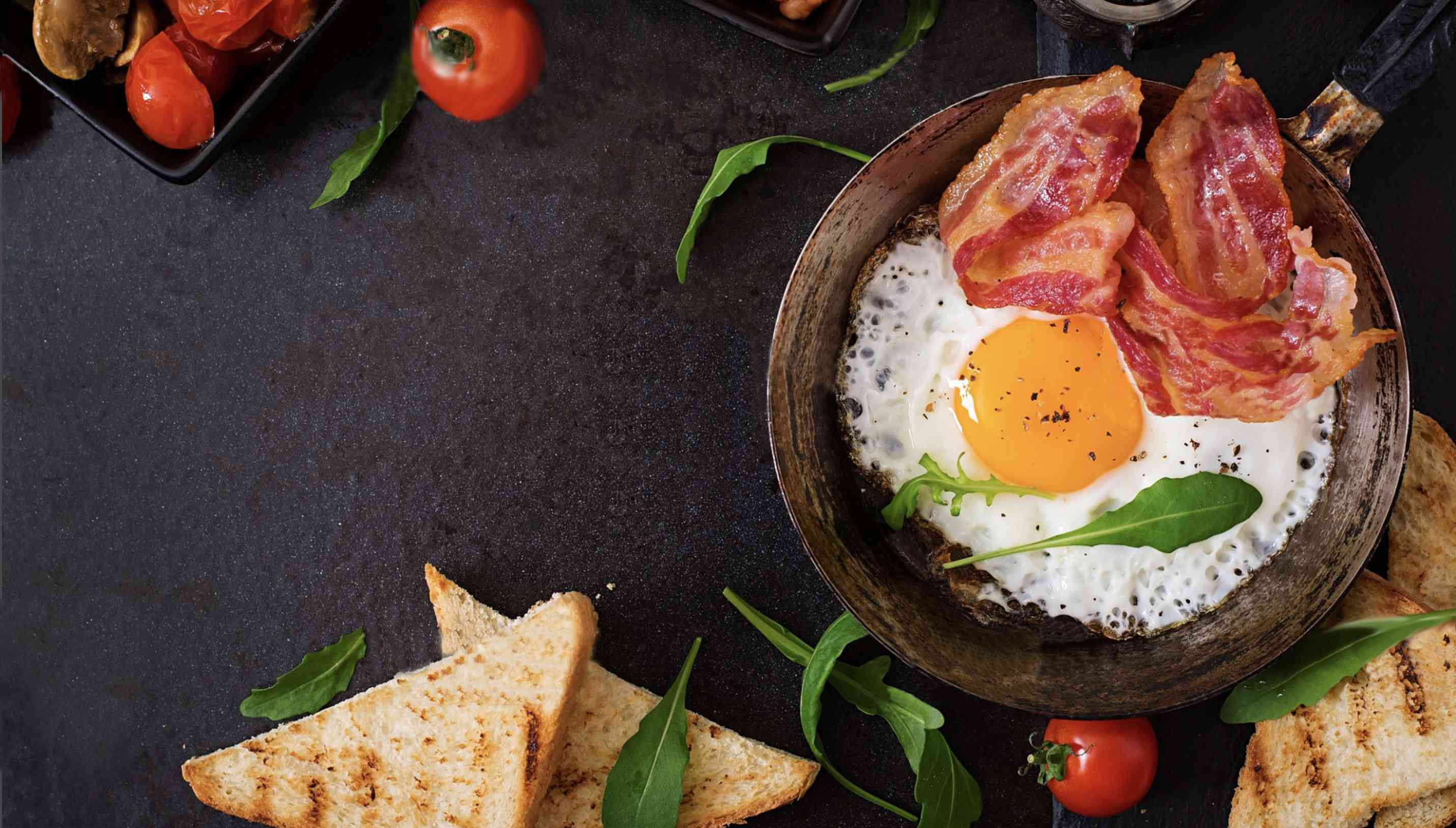 Over head shot of a metal pot with a soft-fried eggs and two strips of bacon. There are some half-slices of toast and small tomatoes on the table