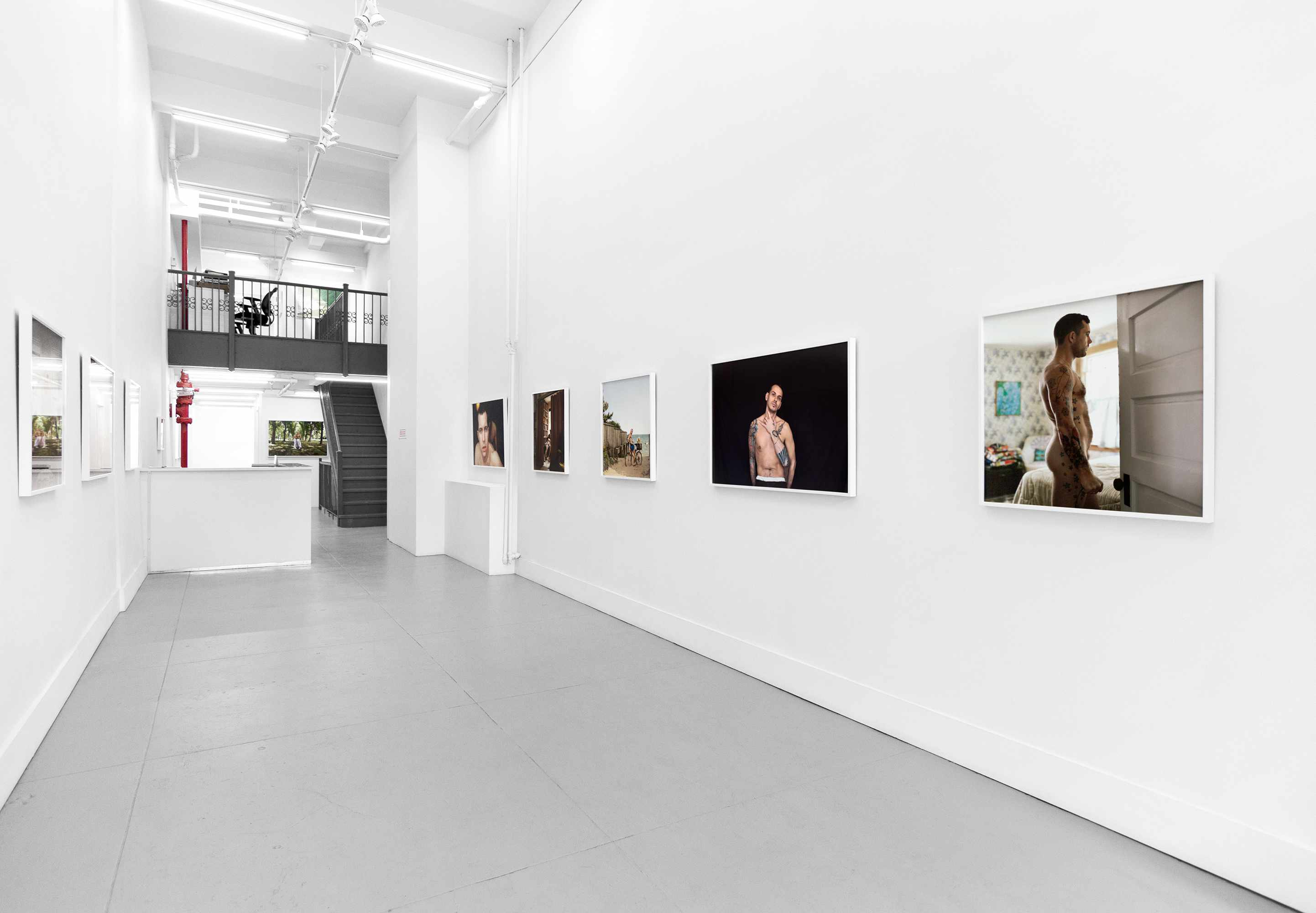 white gallery walls with pictures of a tattooed man on them
