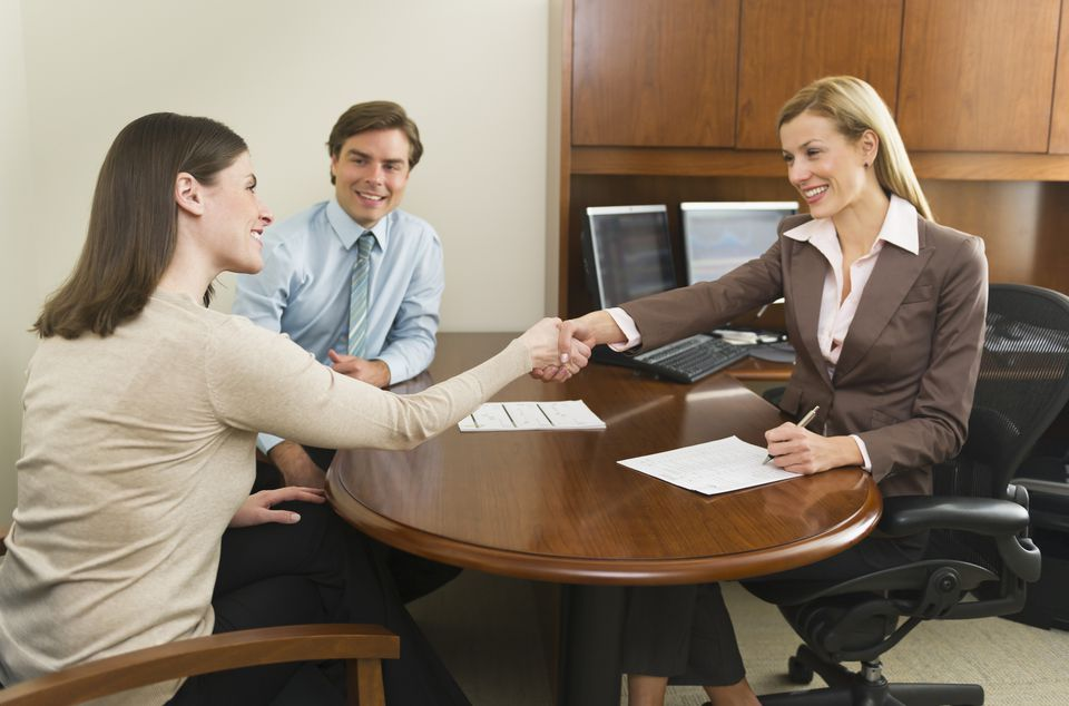 a couple meeting with a business woman in an office