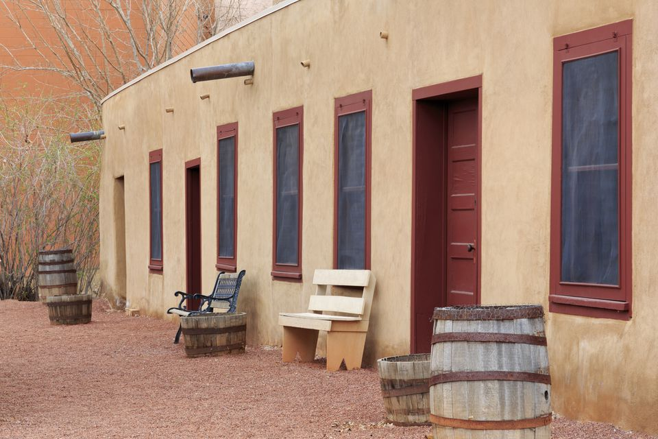adobe building with red doors and windows. There are two benches, three wooden buckets, and two wooden barrels in front of the building