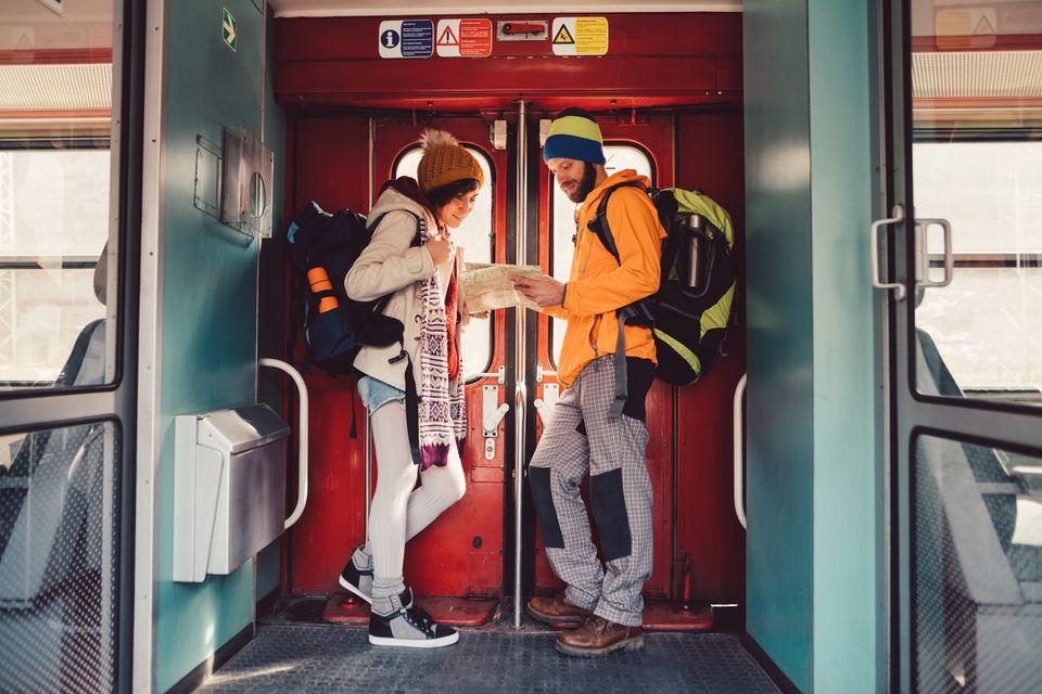Una mujer y un hombre miran un mapa mientras están en un tren