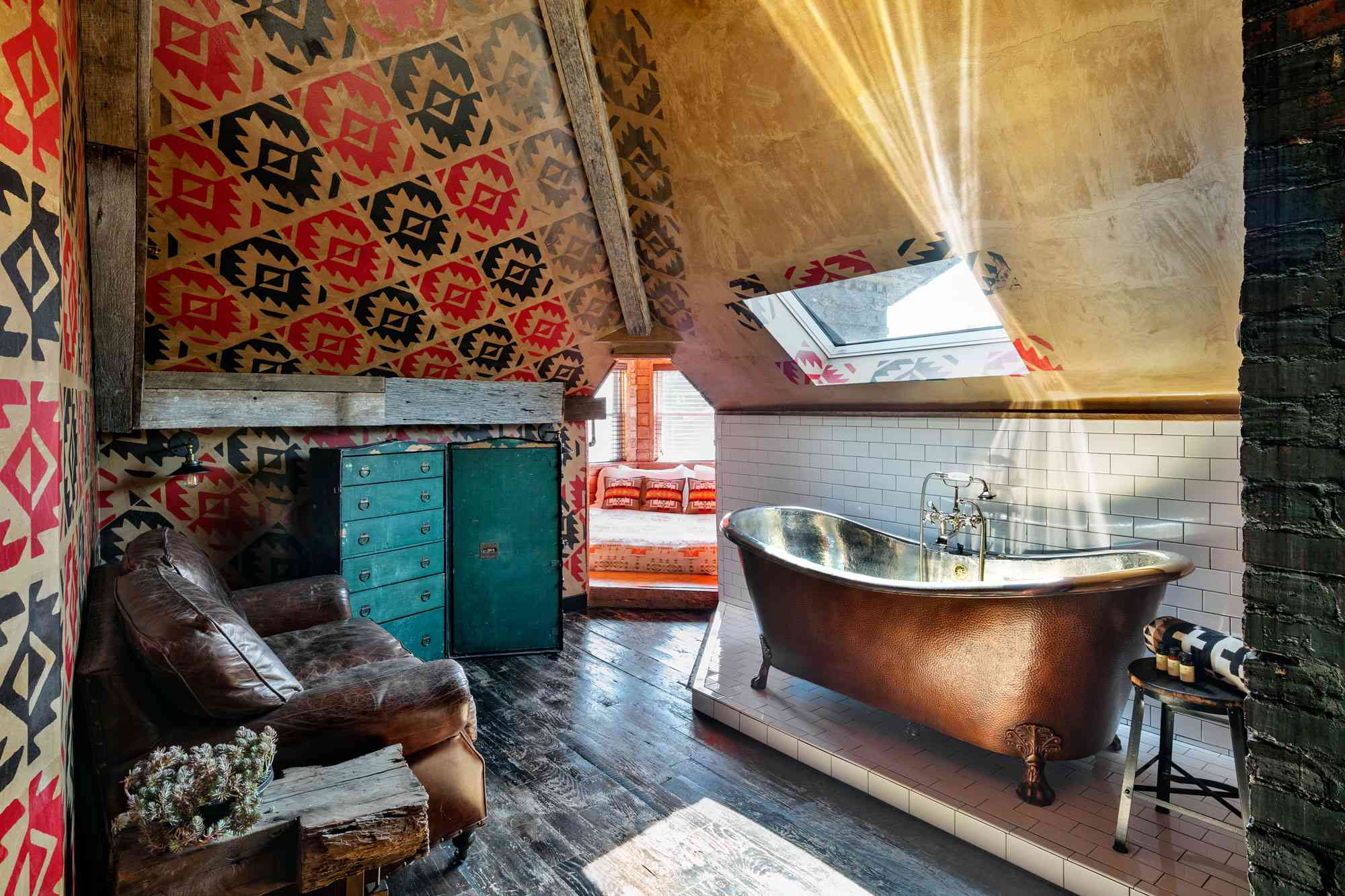 Suite at the Urban Cowboy Bed & Breakfast Nashville with a distressed leather couch in front of a claw foot copper tub with dark hardwood floors