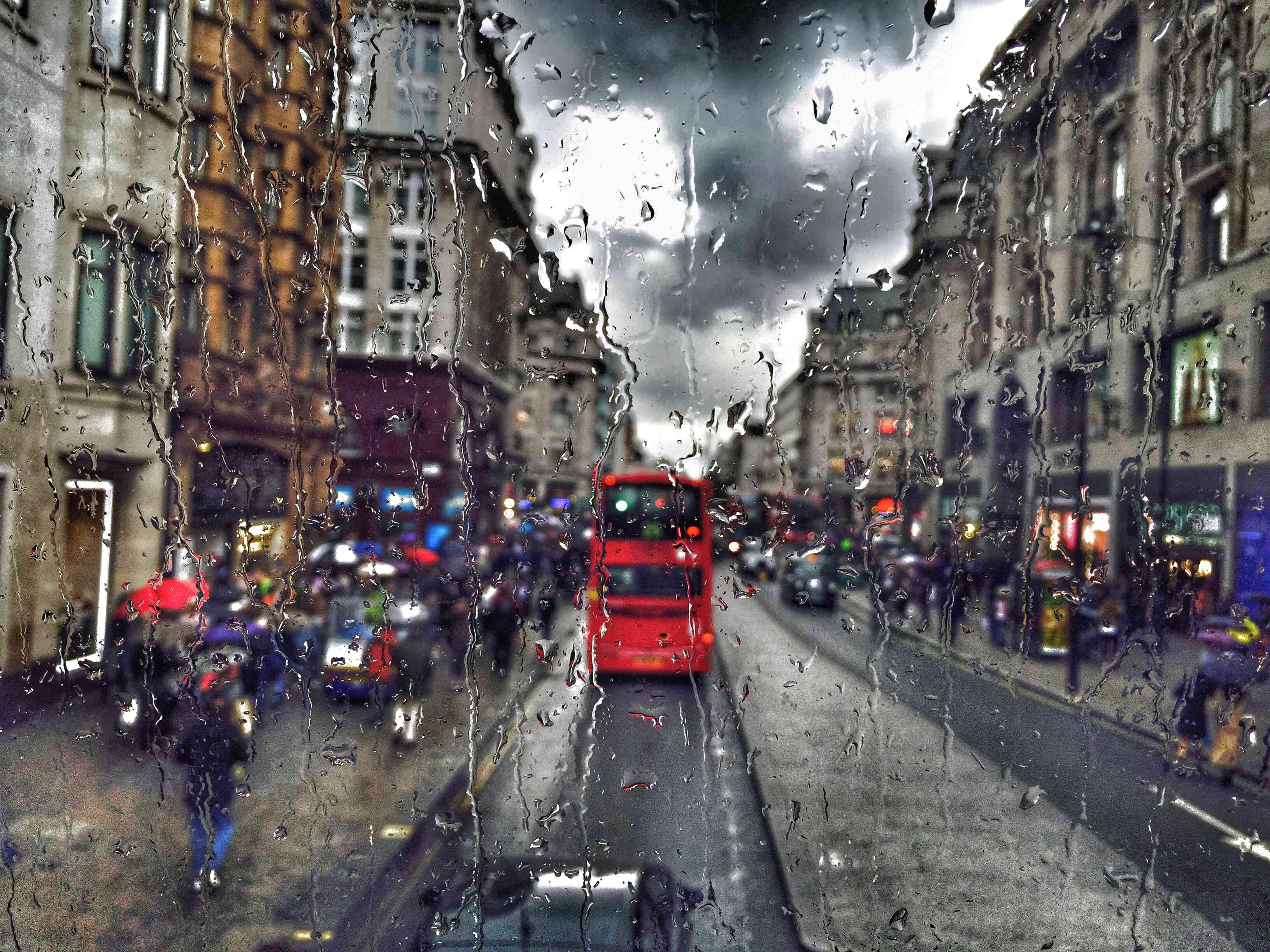Traffic On a Road In England Amidst Buildings Seen Through Wet Glass Window On Rainy Day