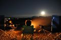 Siblings Sitting On Chairs By Campfire At Field Against Sky During Night