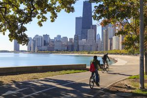 Cyclists riding along Lake Michigan shore with the Chicago skyline beyond, Chicago, Illinois, United States of America, North America