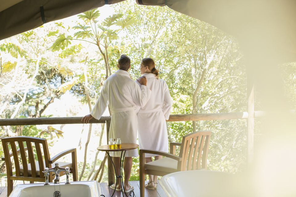 Couple in bathrobes standing in outdoor spa