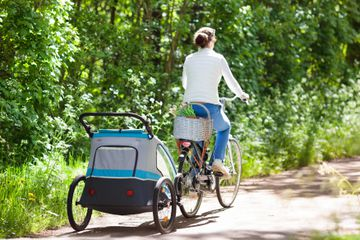 Woman riding bike with trailer attached