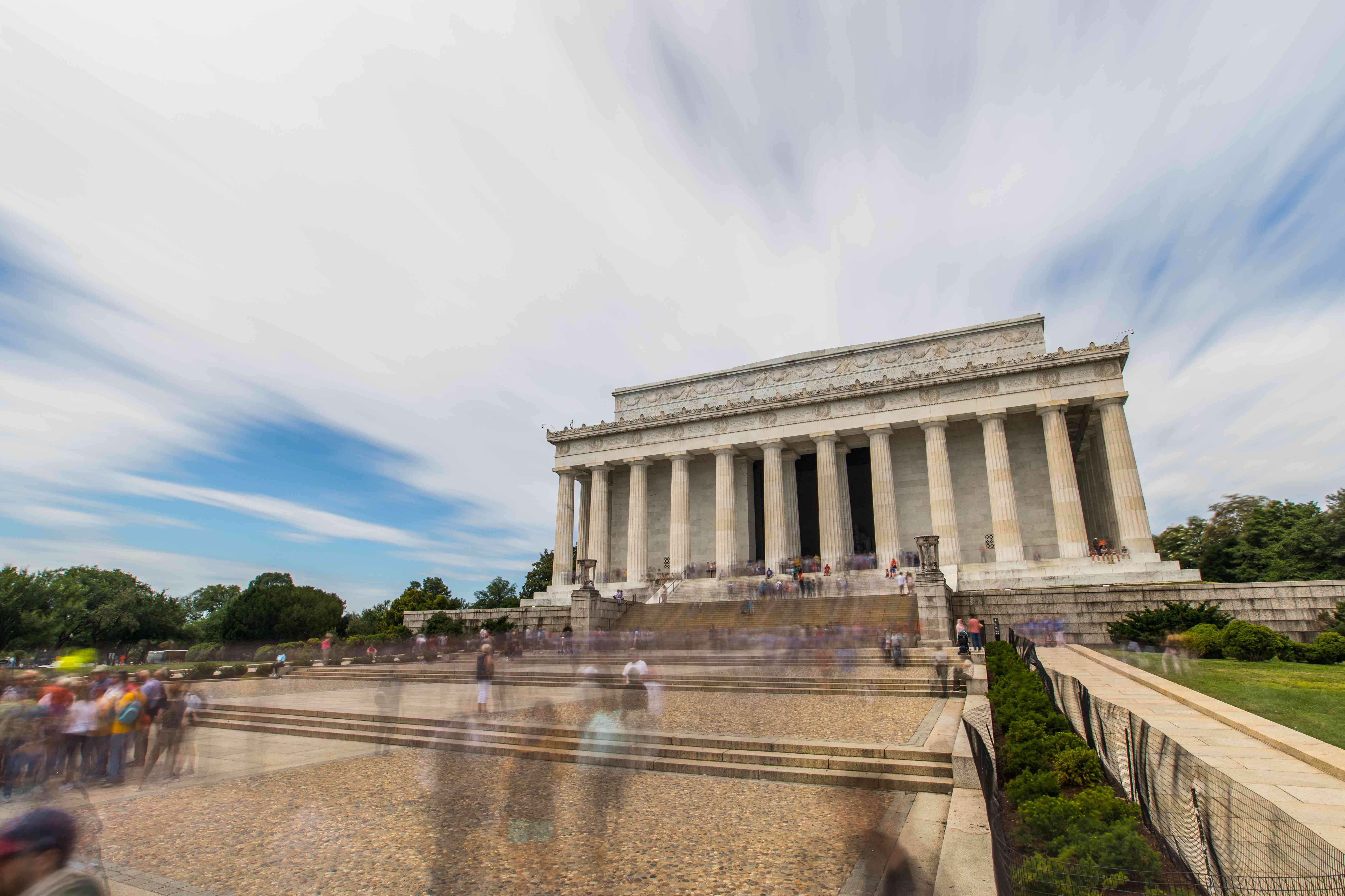 Time lapse shot of people walking past the Lincoln Memorial