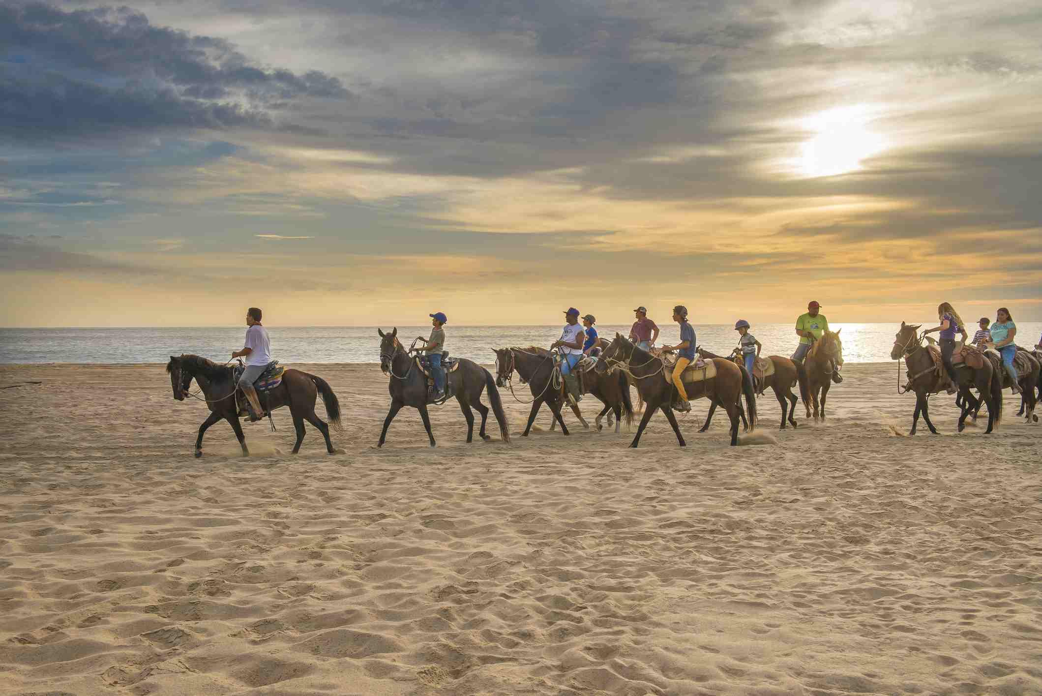 Summertime in PUNTA LOBOS Beach, local people riding horses, Todos Santos, Baja California Sur. MEXICO
