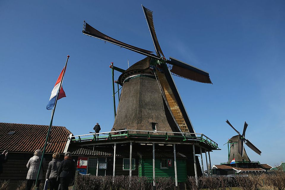 Visitors inspect a spinning windmill at the Zaanse Schans outdoor mueseum on April 1, 2013 in Zaandijk, Netherlands. Zaanse Schans, established in the 1970s, is a collection of original houses and windmills, many of them still functioning, from the nearby Zaanstreek region. Zaanse Schans attracts approximately 900,000 visitors a year.