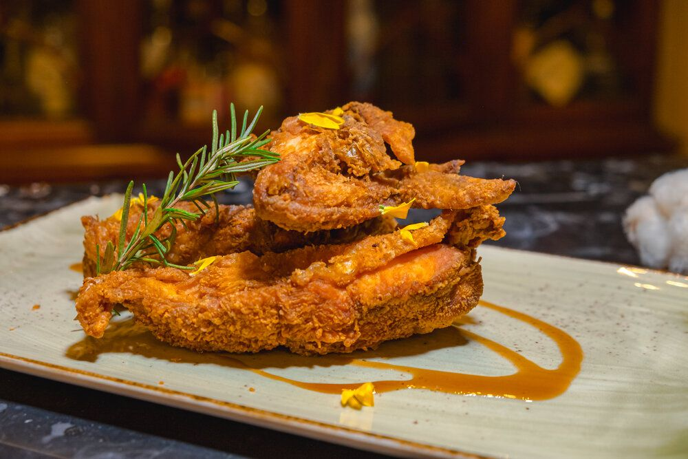 three pieces of fried chicken on a rectangular ceramic plate. The chicken is garnished with a sprig of rosemary