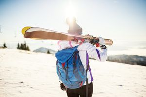 Young woman after skiing on sunny day with backpack
