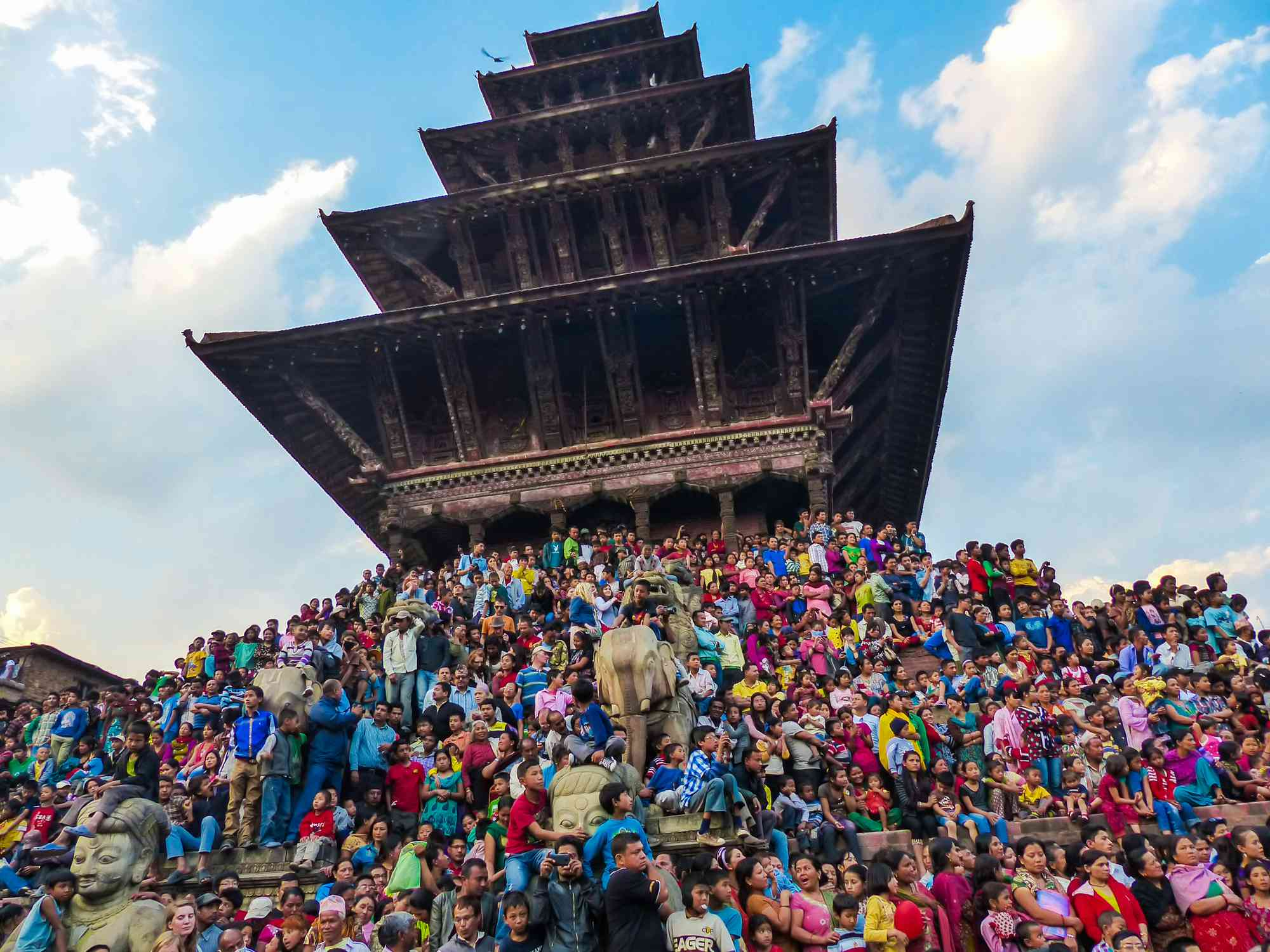 crowd of people beneath a tiered pagoda temple