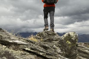 A man in black pants standing on a mountain peak