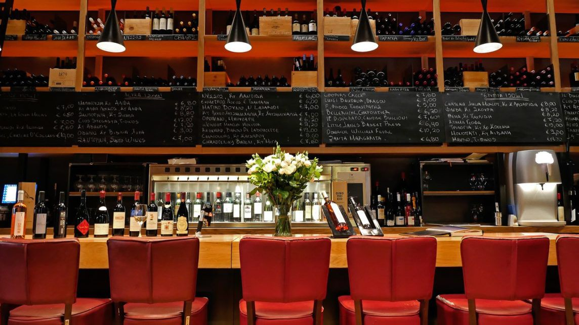 Red chairs at a wooden bar with black boards over the bar and wine bottles on the wall at By the Glass in Athens