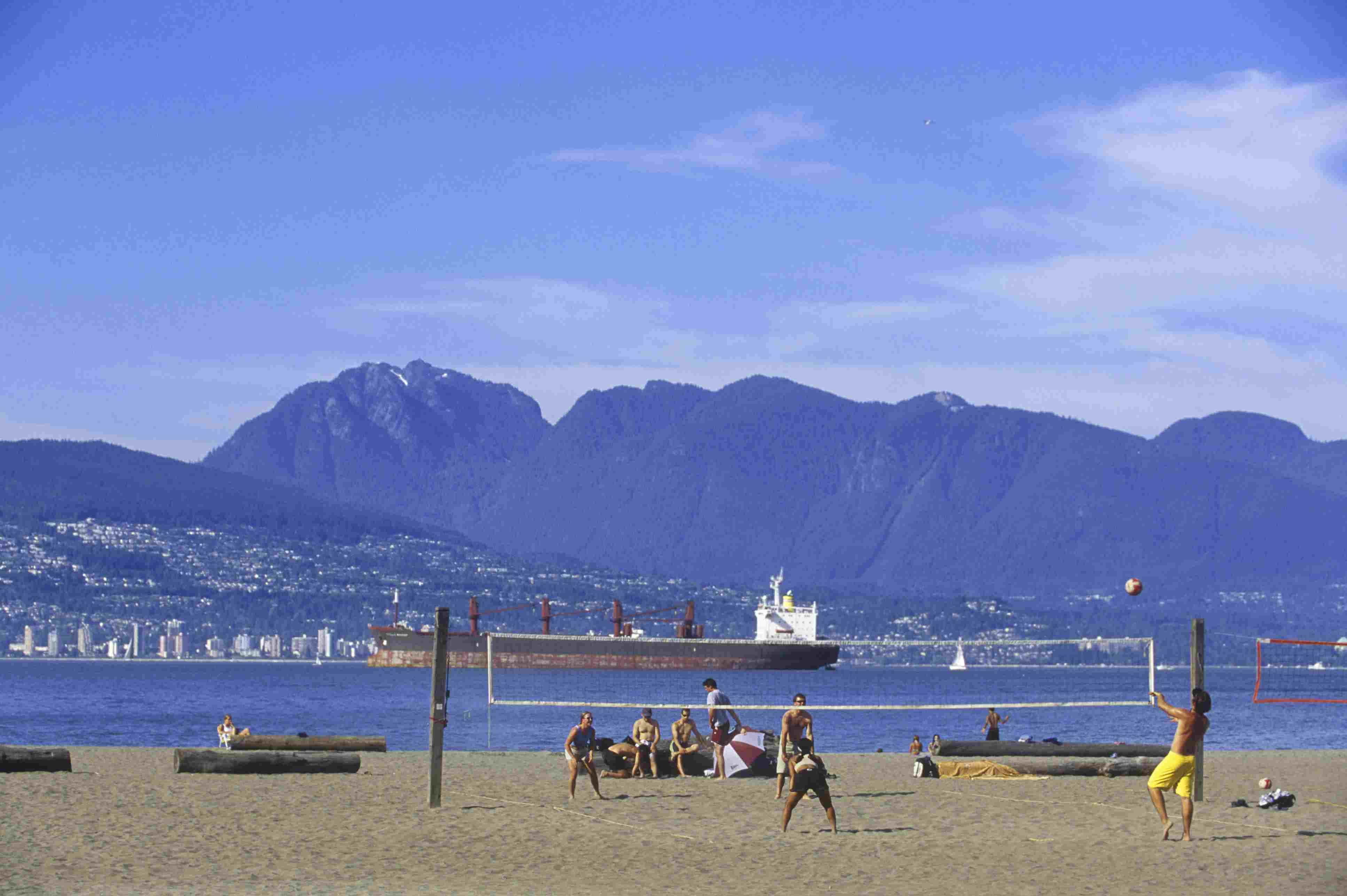 People playing volleyball on Kitsilano Beach, Commercial ship in English Bay and North Shore beyond, Vancouver, British Columbia, Canada.