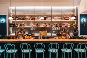 Blue chairs at a wooden bar with shelves fully stocked with liquor