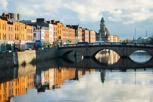 Buildings along the quays reflected in the river Liffey in Dublin City, Ireland