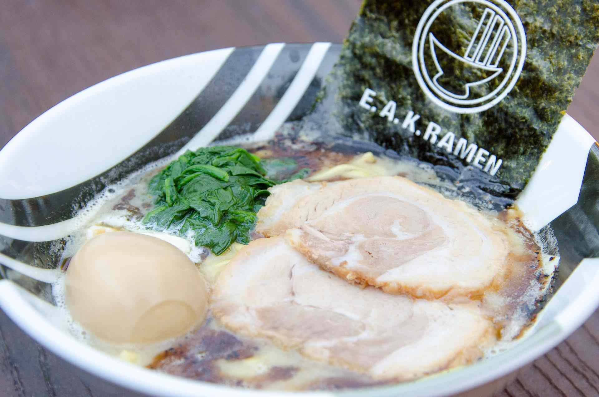Closeup of ramen with a whole egg, spinach, and a pieced of dried seaweed from EAK Ramen
