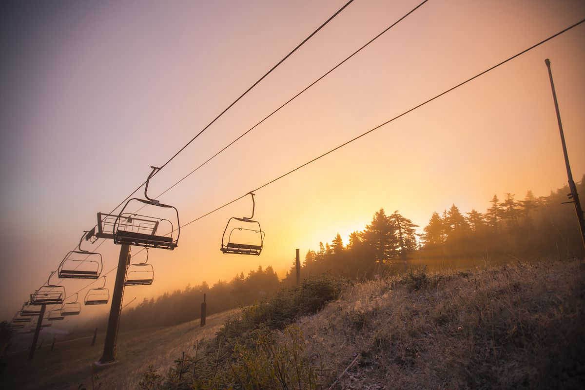 Killington's ski lifts over a snowy slope with the sunset in the west.