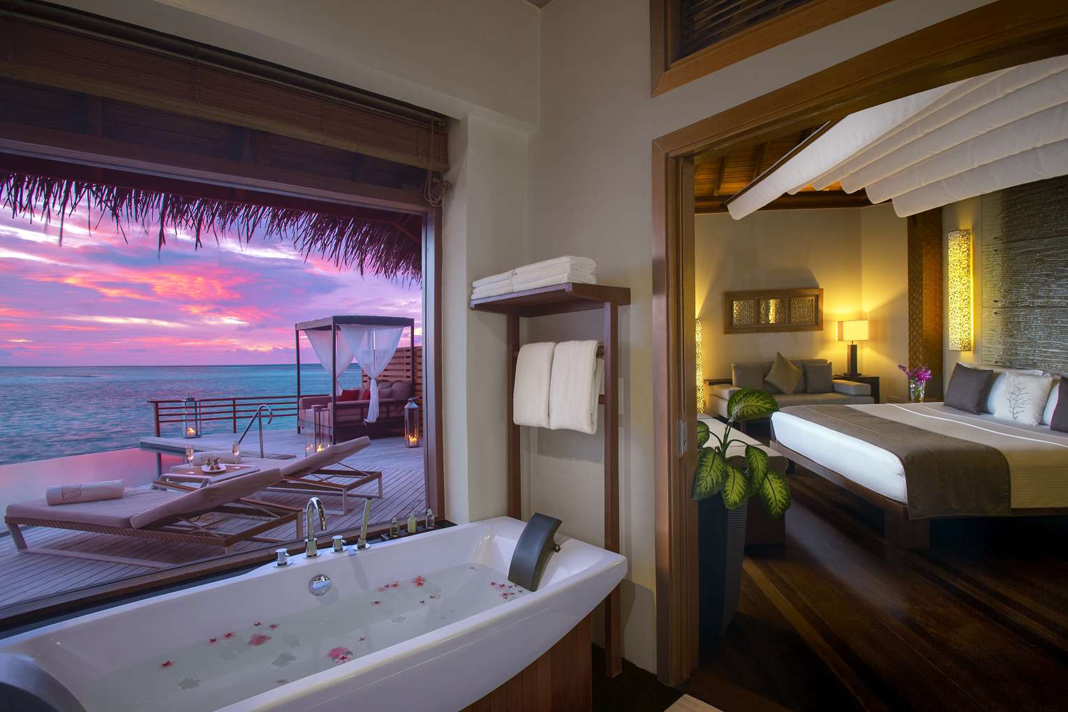 Photo of a villa interior with a bathtub to the left of frame and fed to the right. There is a window behind the tub that shows a pink and blue sunset and water front lounge chairs