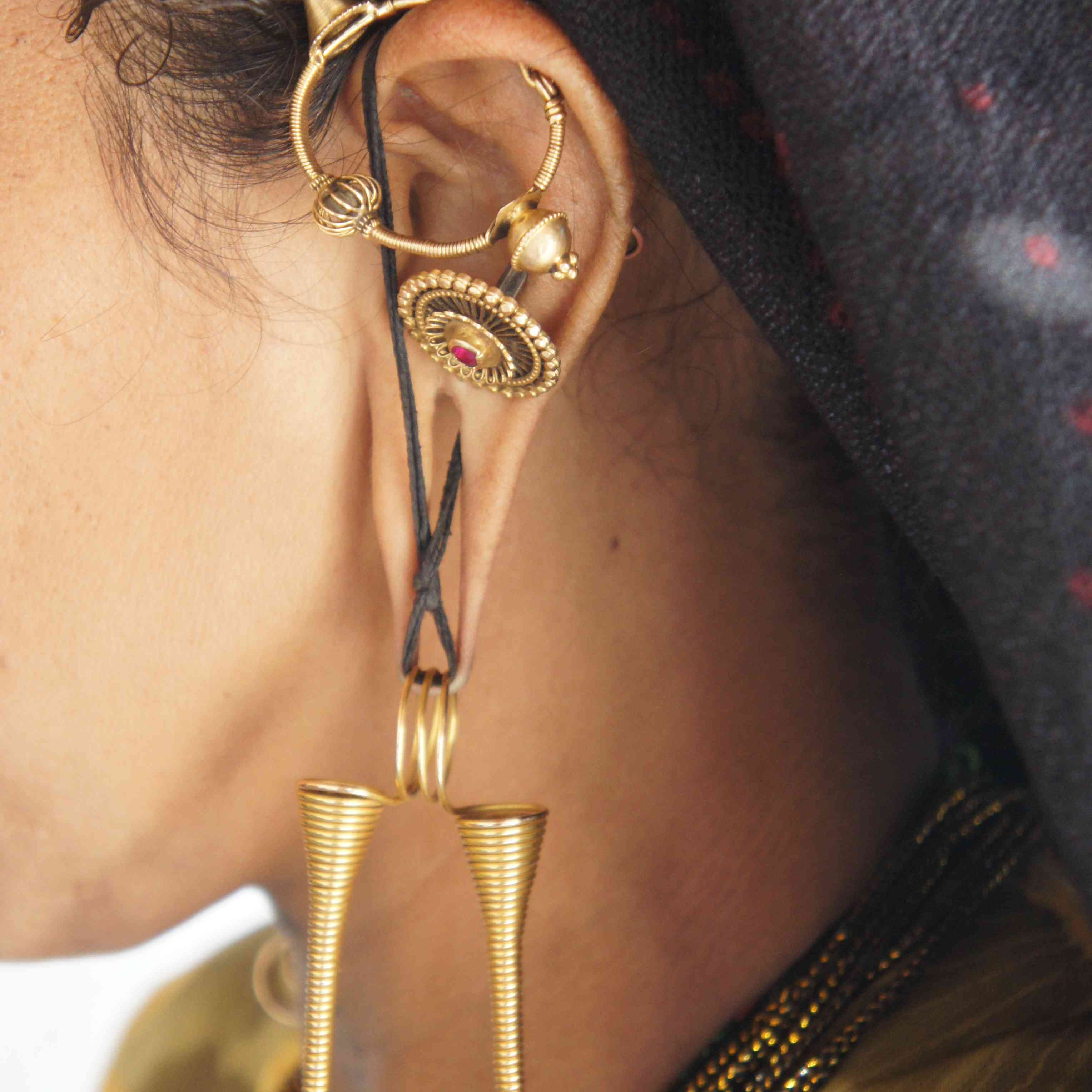 elaborate gold earrings on an Indian woman with stretched earlobes