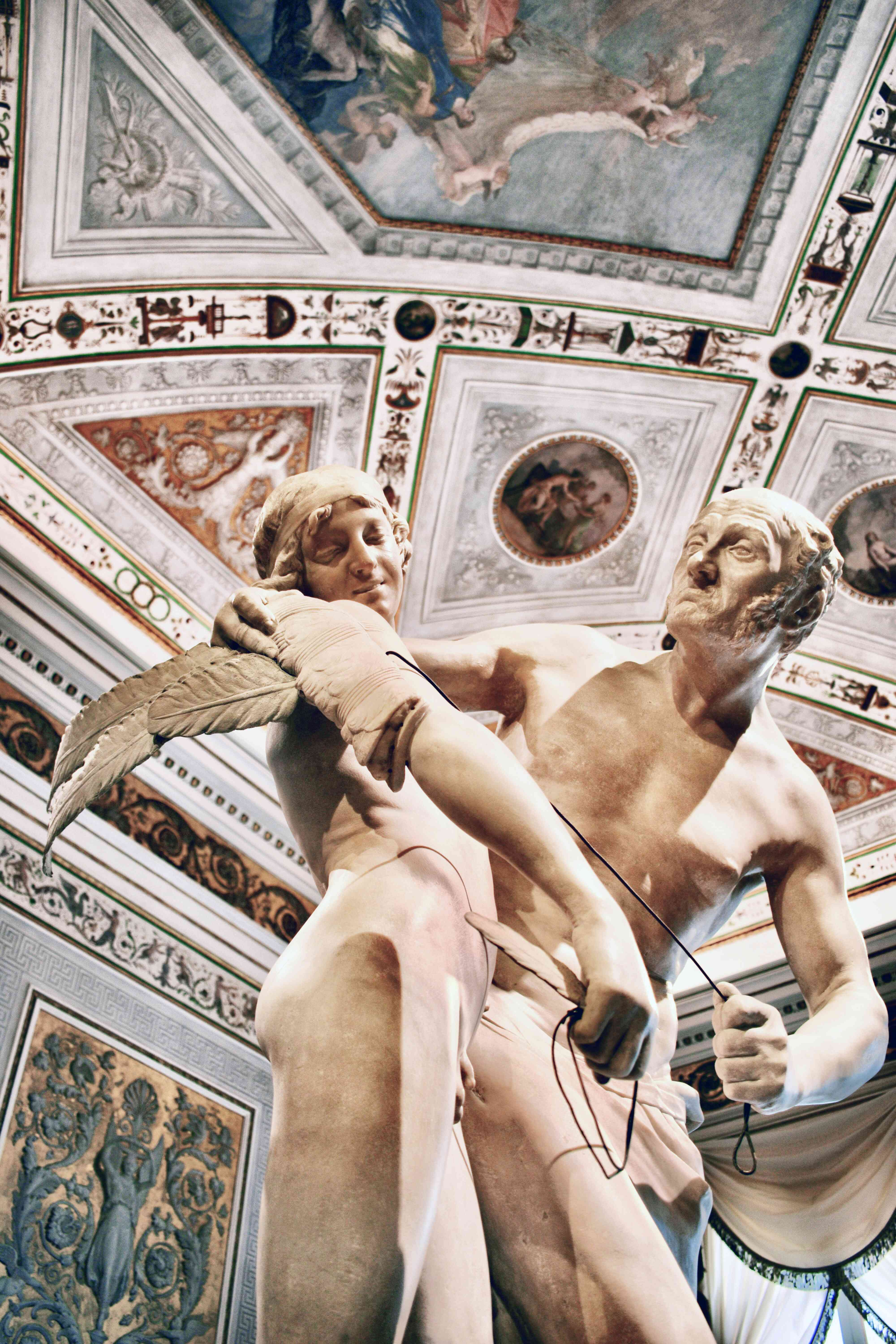 A marble statue with a detailed painted ceiling in the Museum Civico