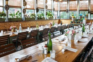 Long dining table with place settings, flowers and green bottles of water