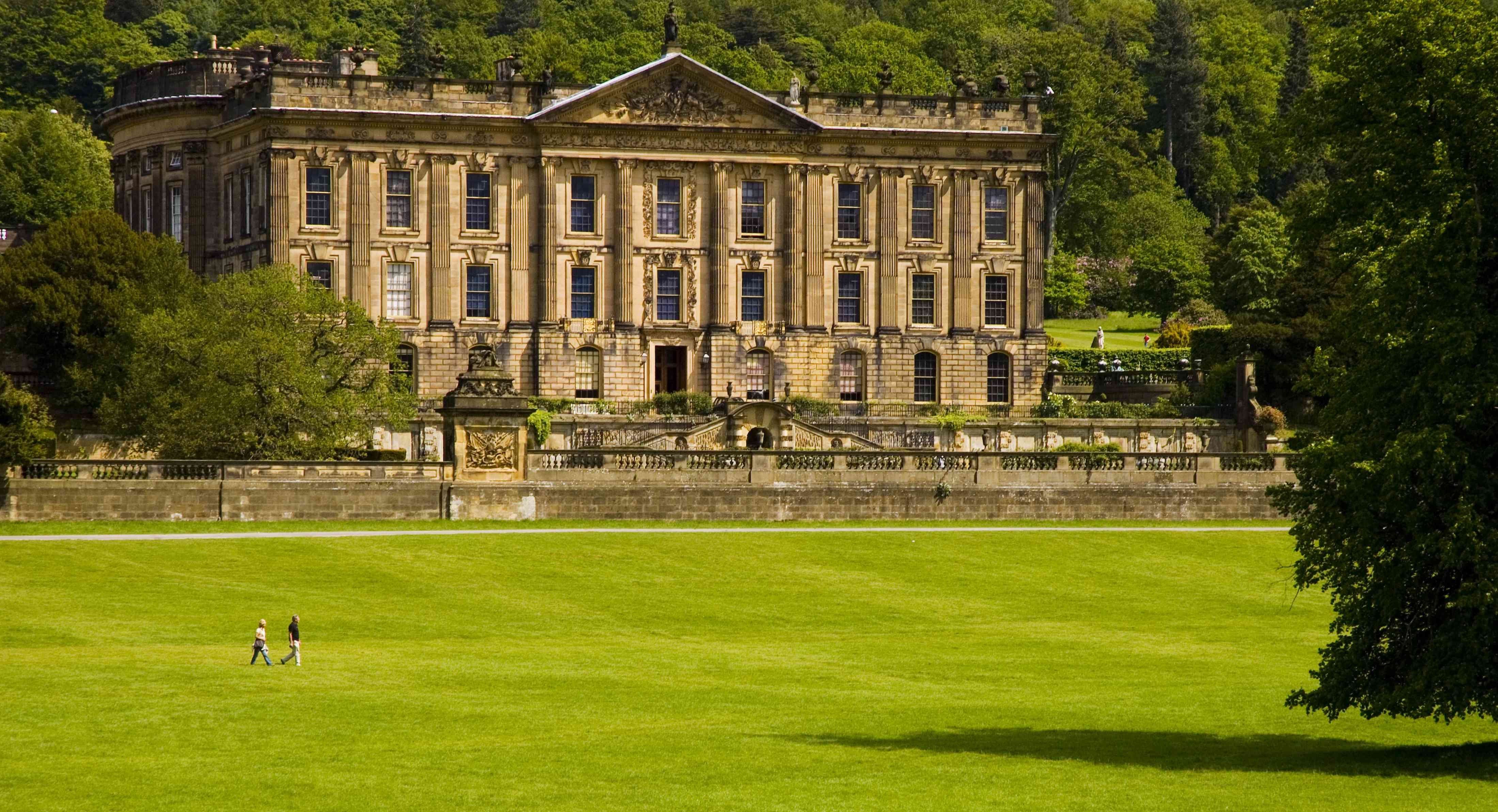 large field in front the aged Chatsworth House with two people walking across the lawn