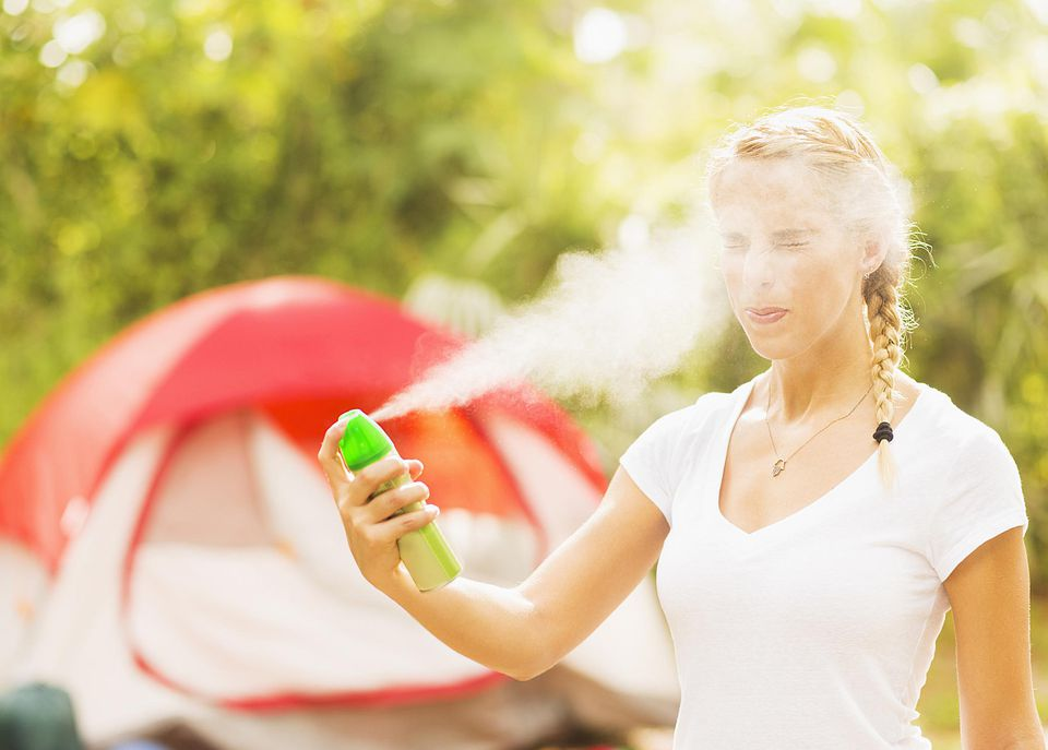 Woman spraying mosquito repellent in face