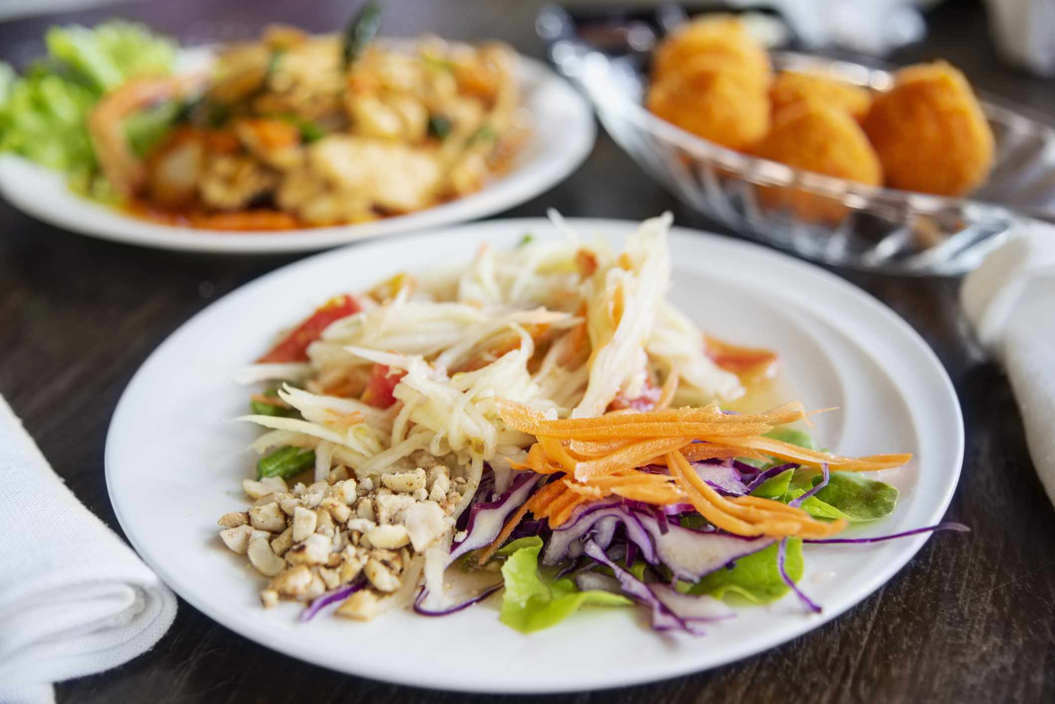 Som tam salad on a pate with other thai dishes in the background
