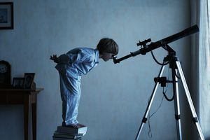 Boy (4-6) standing on stack of books looking through telescope