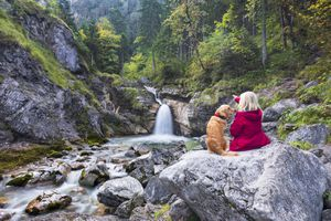 Woman with Golden Retriever dog enjoys the silence at the waterfall in the Alps