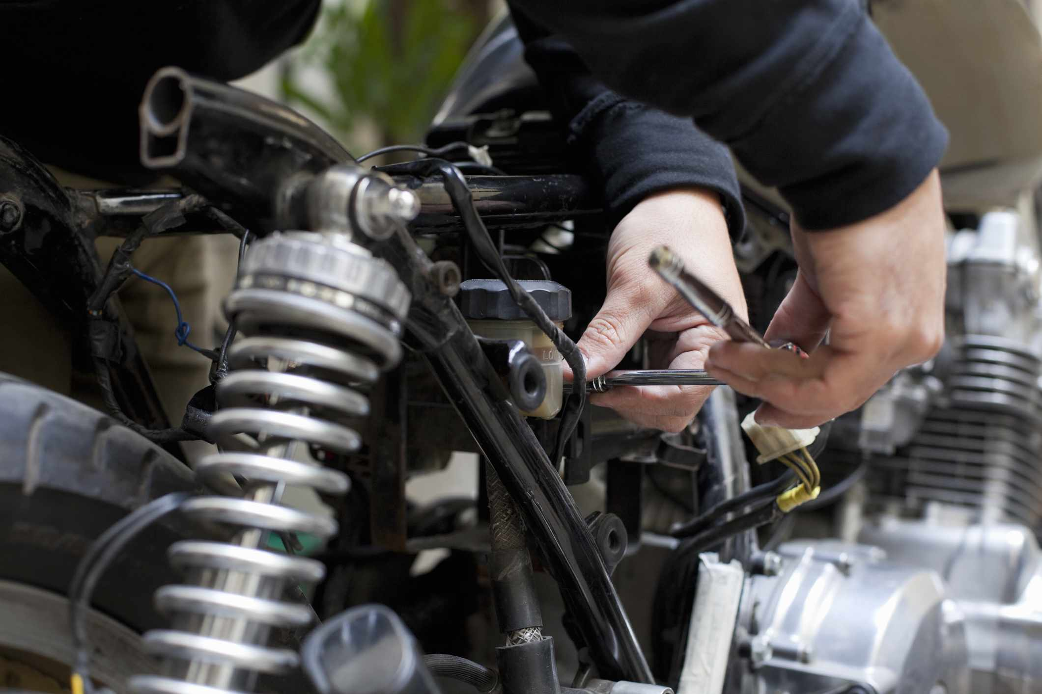 Person using a metal tool to fix and motorized bicycle