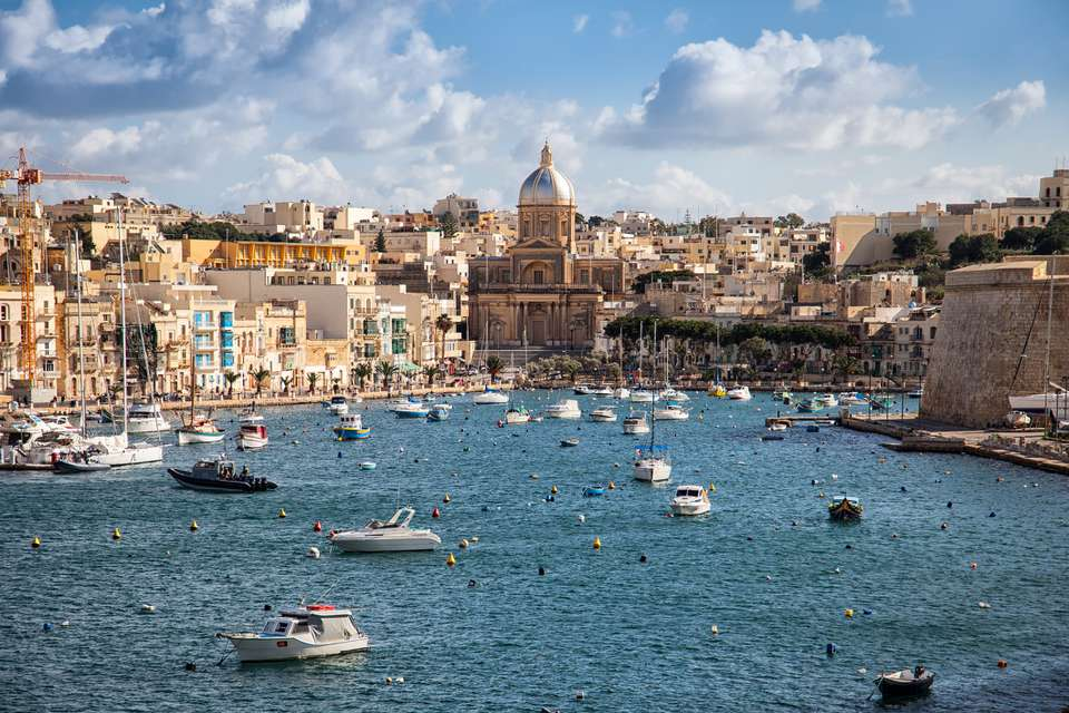 Boats in Grand Bay at Valletta, Malta with the city in background
