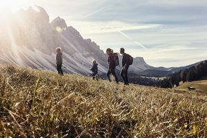 a family goes for a hike with mountains in the background.