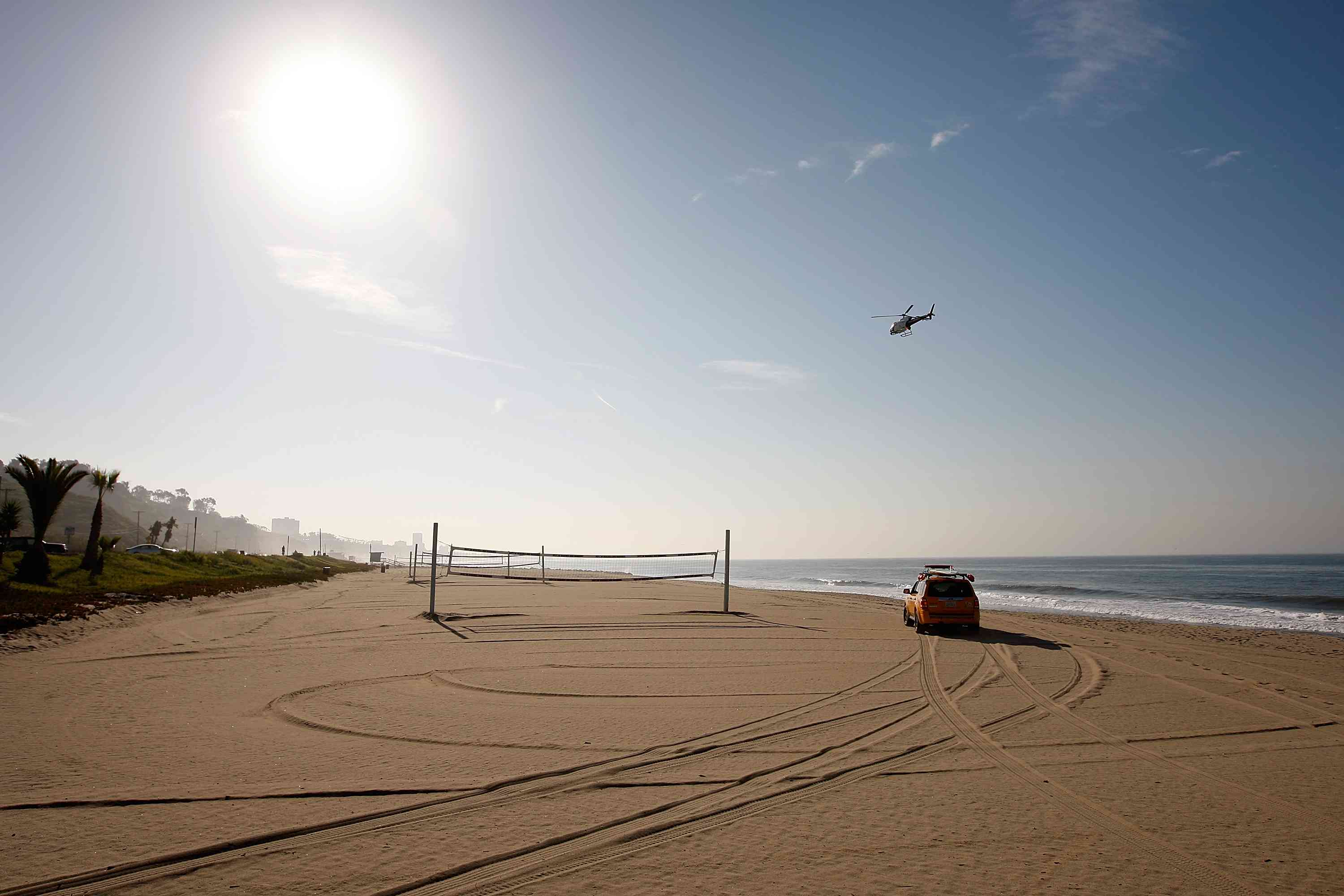 car on an empty beach with volleyball nets. There is a helicopter in the sky above