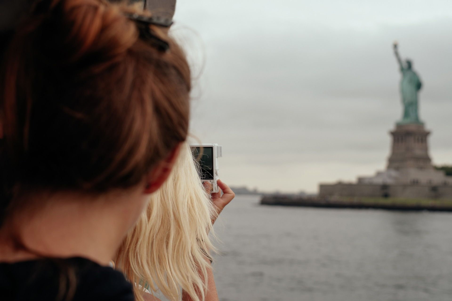 Tourists taking photo of Statue of Liberty