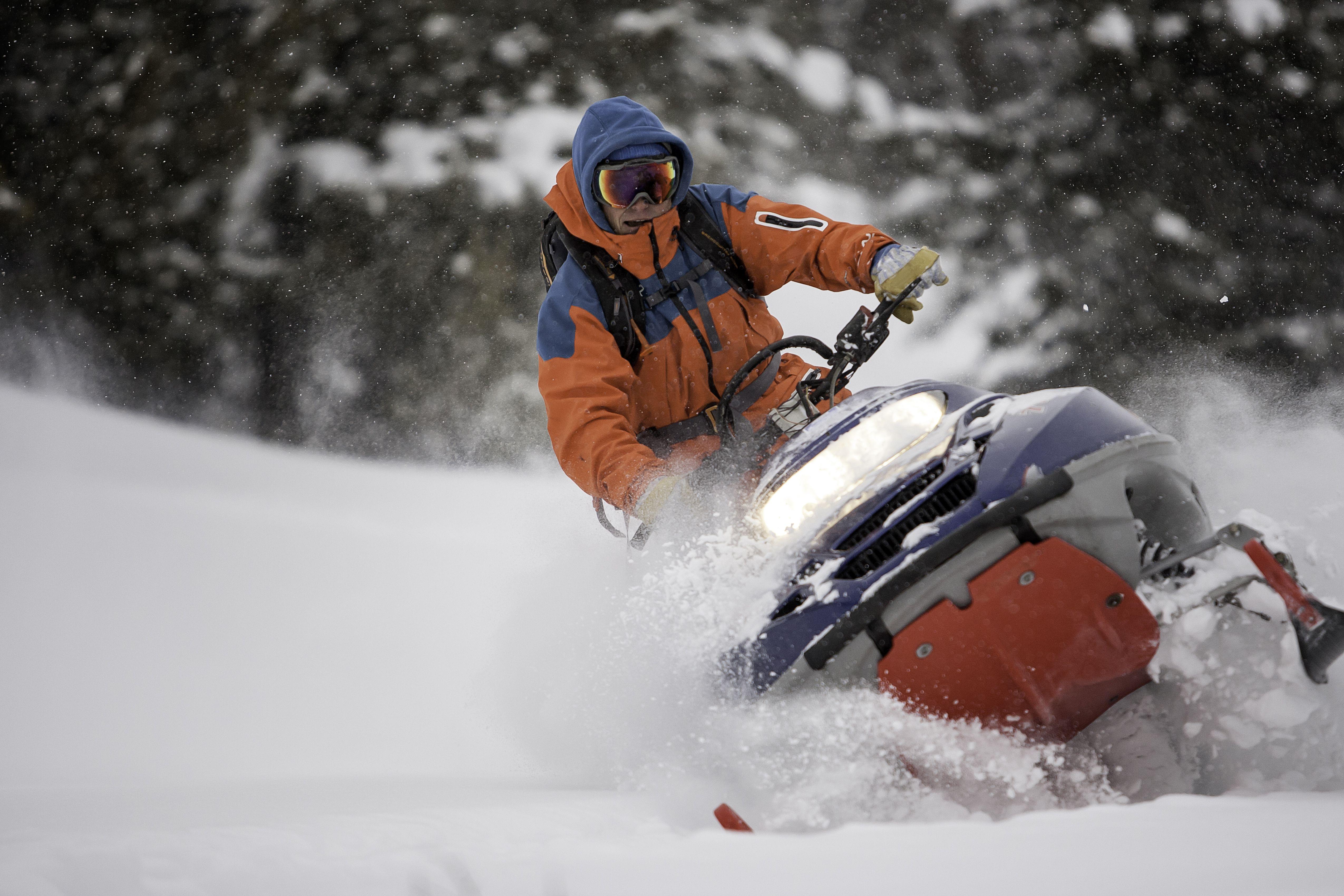 Guy on a snowmobile taking a powder turn.