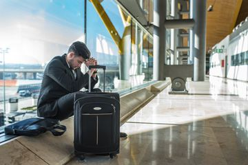Young man at airport waiting with luggage