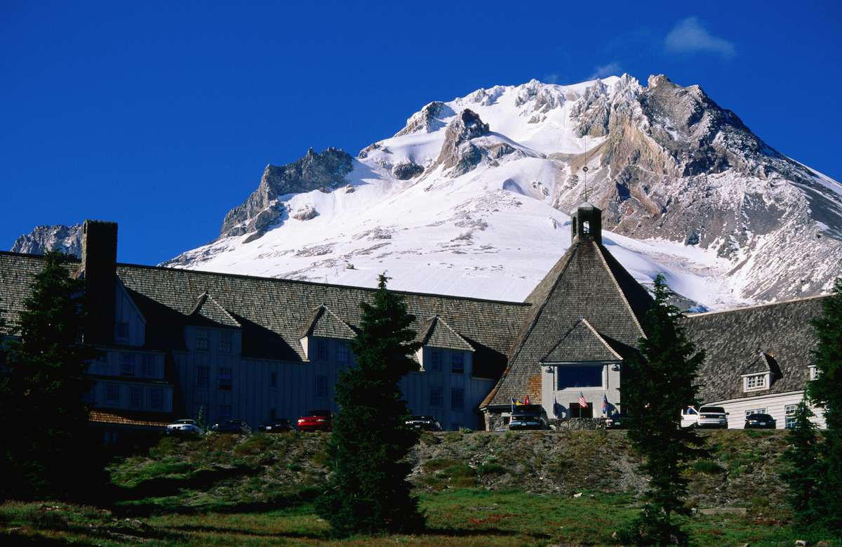 A large mountain lodge stands at the foot of a snowcapped peak.
