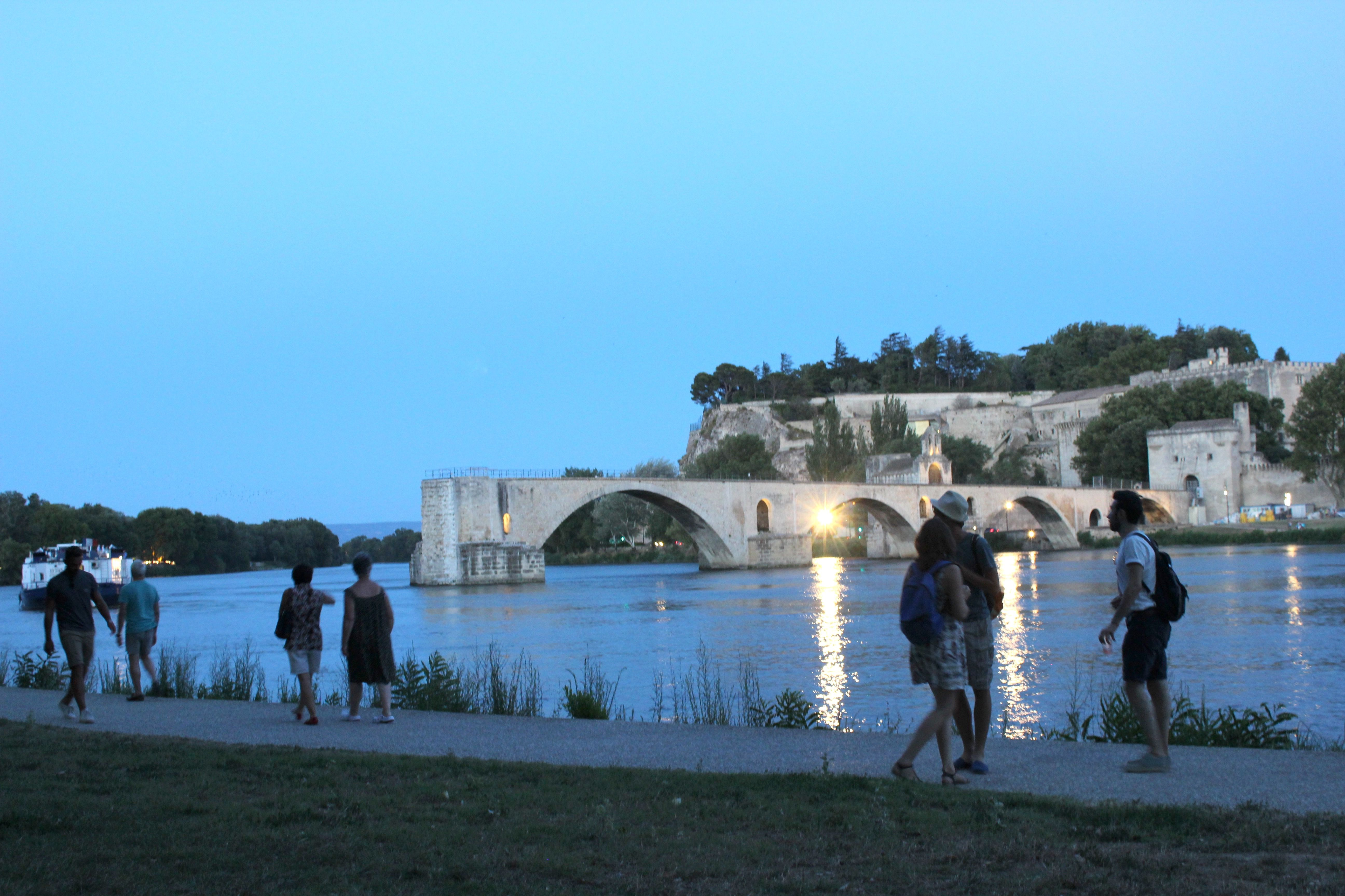 People walk alongside the water at night with the Pont St-Bénézet in the background