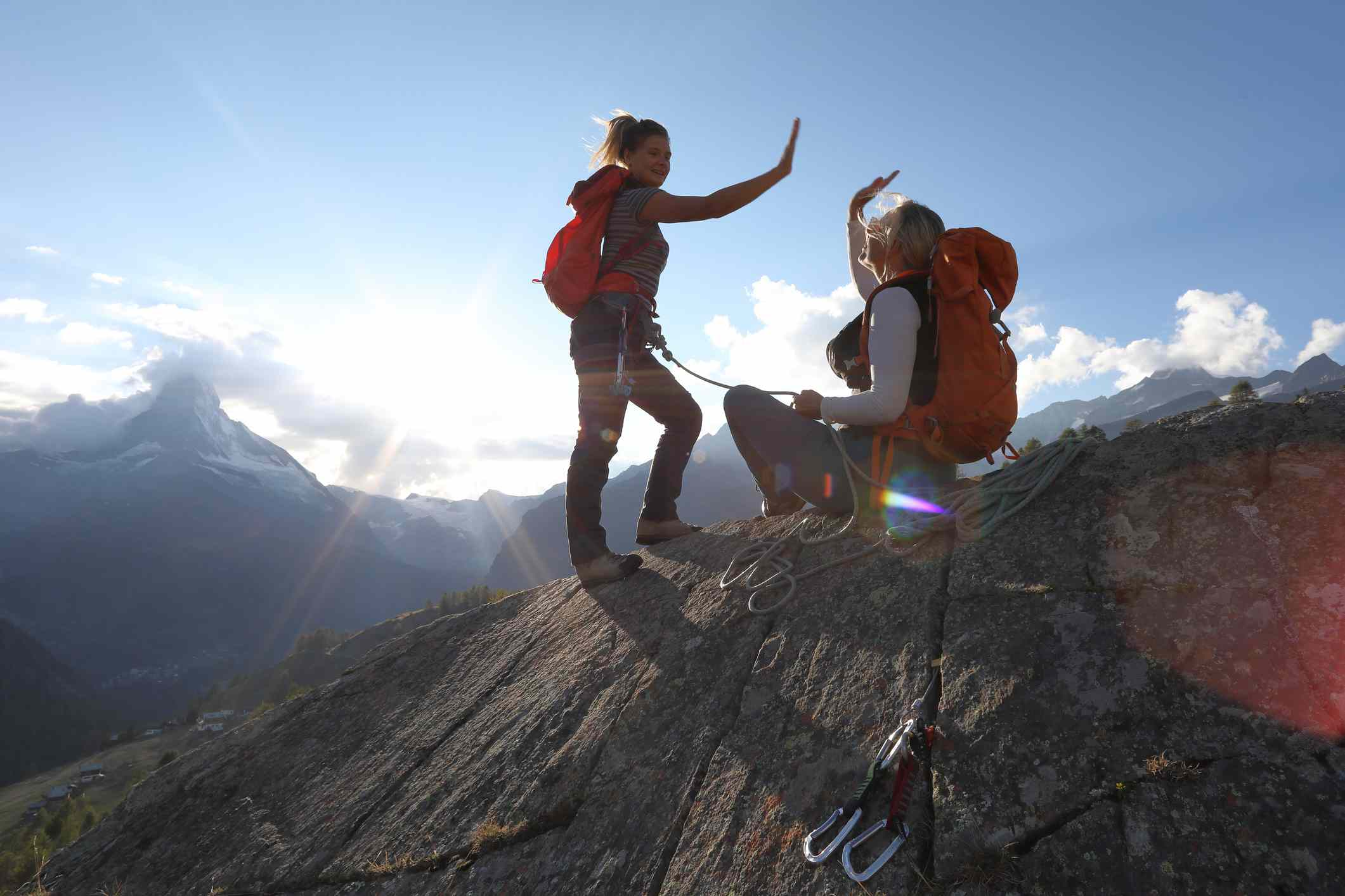Mother and daughter ascend rock cliff, exchange 'high-fives'