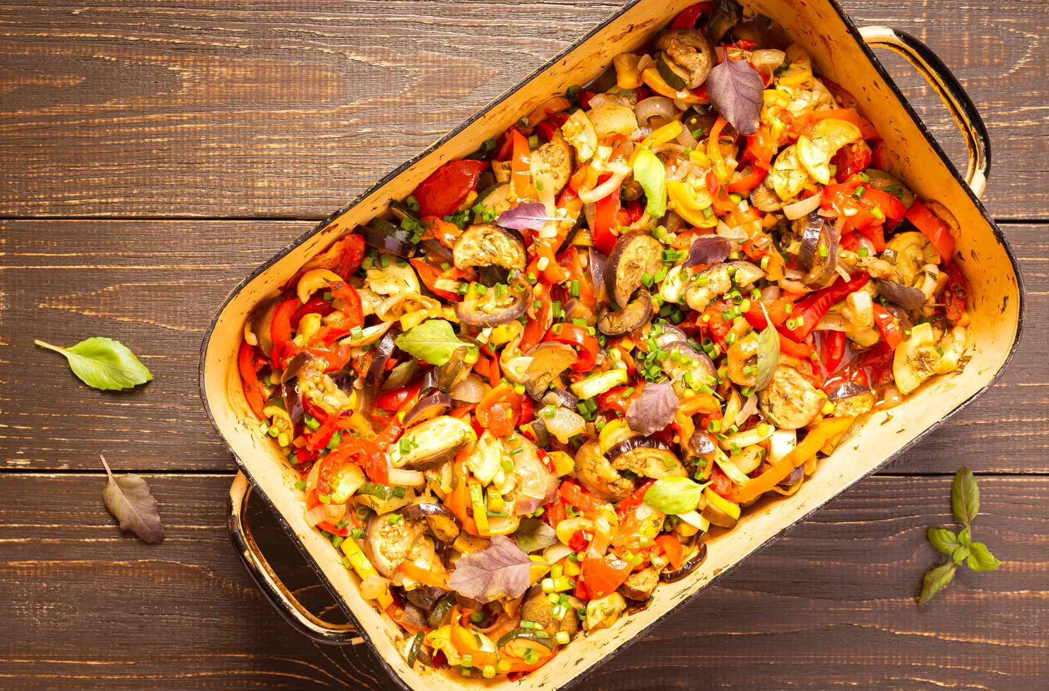 Stewed vegetables in a rectangular pot, eggplant with zucchini and tomatoes, sweet and hot peppers and spices,